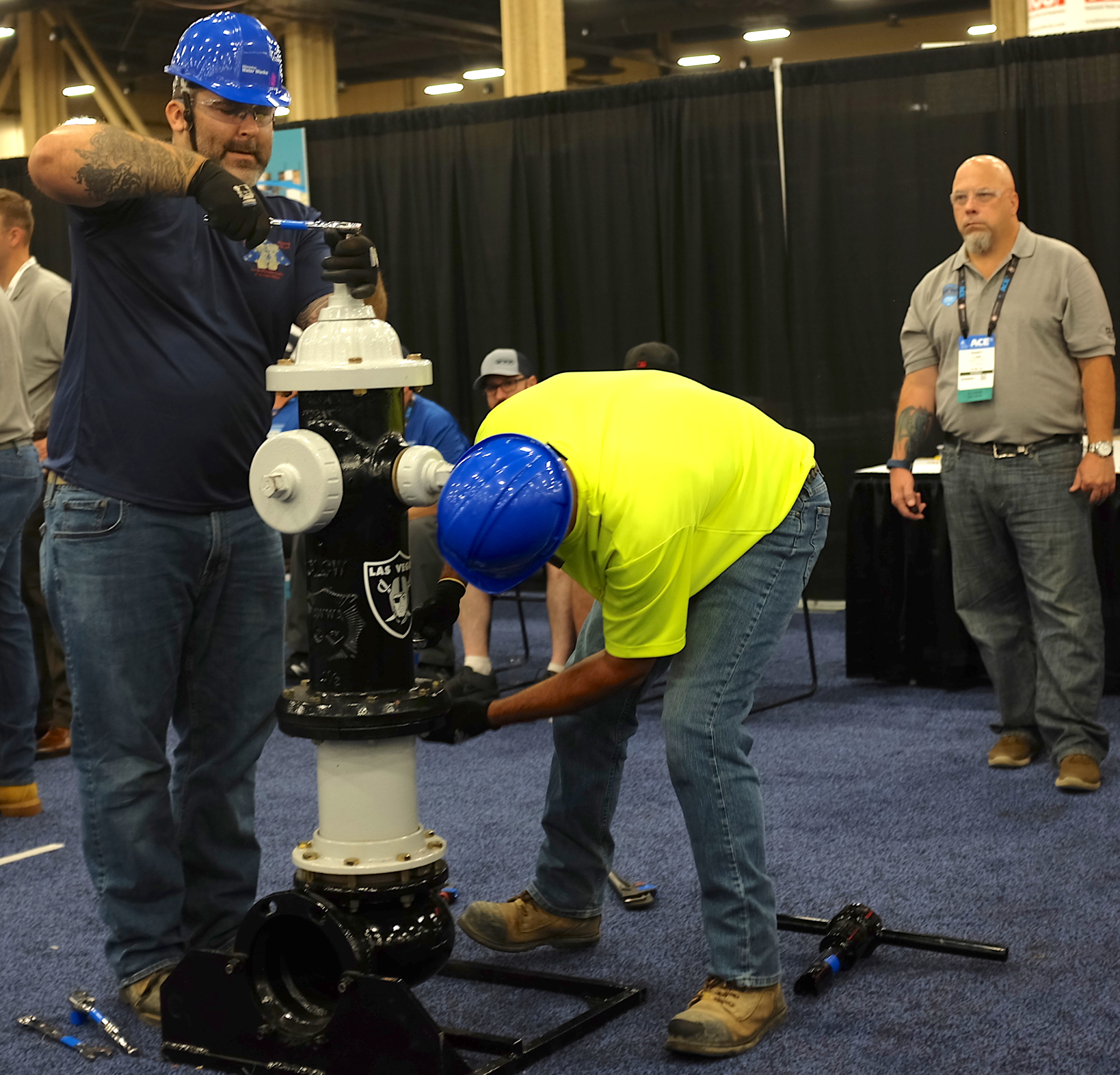 Workers from the city of Milwaukee participate in the Hydrant Hysteria competition to assemble a hydrant as quickly as possible